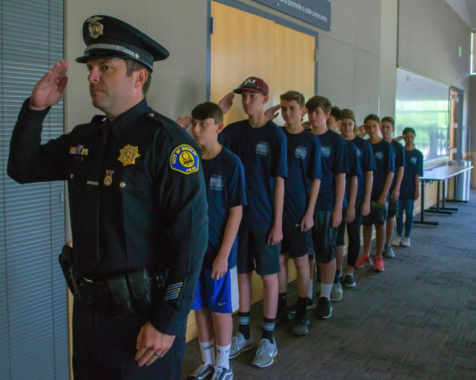 Officer Duckham leads a group of Junior Police Academy students in a salute during the summer of 2018.