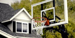 photo of basketball hoop with home in background